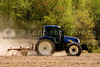 A farm tractor powing an open field.