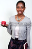 A young African American student teenager holding a book and an apple