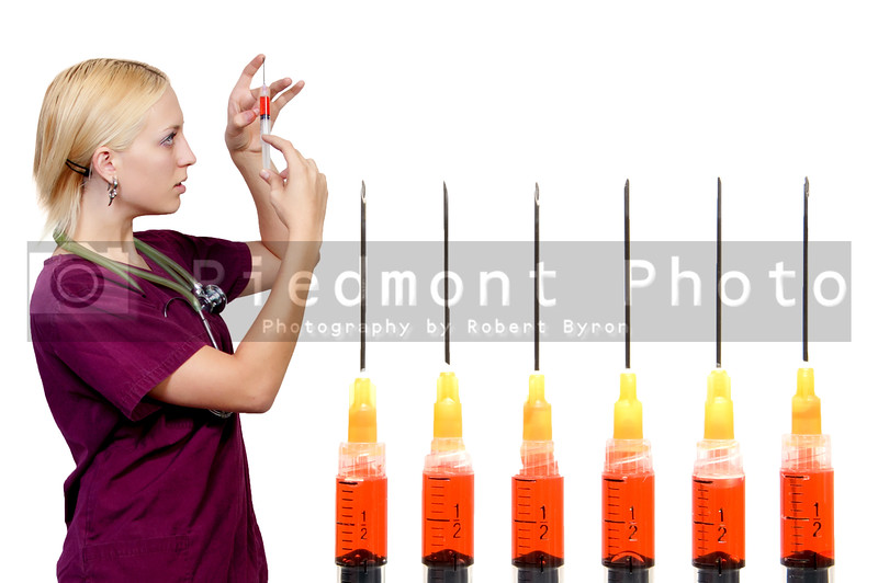 A beautiful blonde woman medical doctor preparing an injection in a syringe