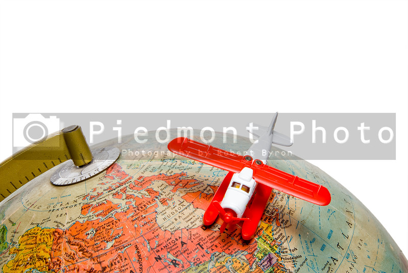 A toy airplane flying over a globe