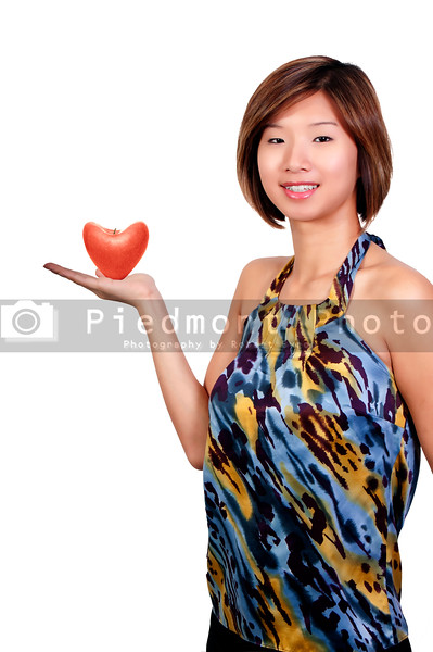 A young Beautiful Asian Woman holding a healthy heart shaped apple