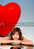 A big red heart behind a beautiful young Asian woman