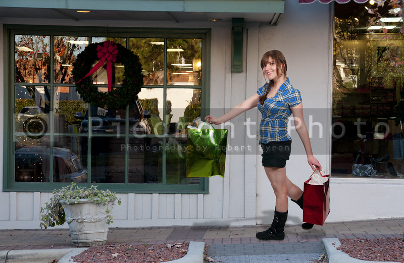A beautiful young woman on a shopping spree in front the stores of a strip mall