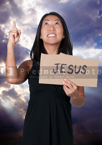 A beautiful young Asian woman holding up a Jesus sign