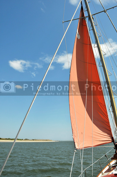 A sailboat with sails open out on the sea