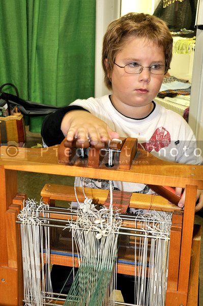 A young boy operating an old handloom