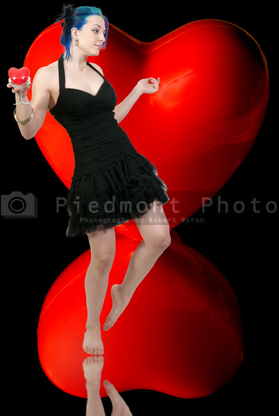 A beautiful young woman holding a Valentines Day heart in a champagne glass