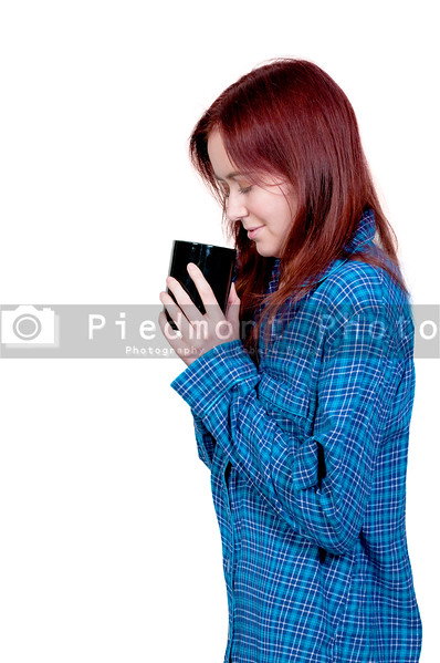 A beautiful young woman drinking and smelling coffee in her pajamas