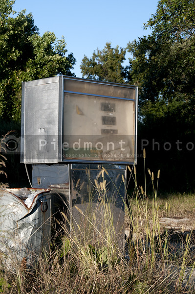 A run down gas pump at an abandoned petrol station.