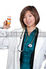 A beautiful young female doctor on her rounds holding a prescription bottle of medicine pills