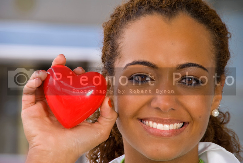 A beautiful cardiologist holding a red heart