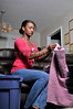 A young African American woman folding clothes