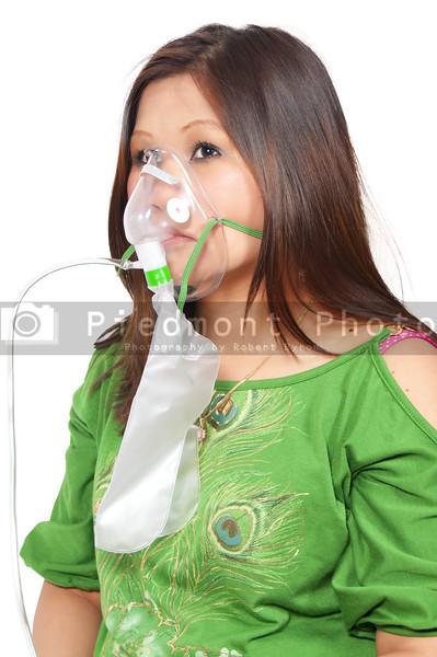 A beautiful young woman wearing an oxtgen mask