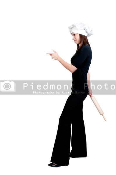 A beautiful young woman chef holding a rolling pin