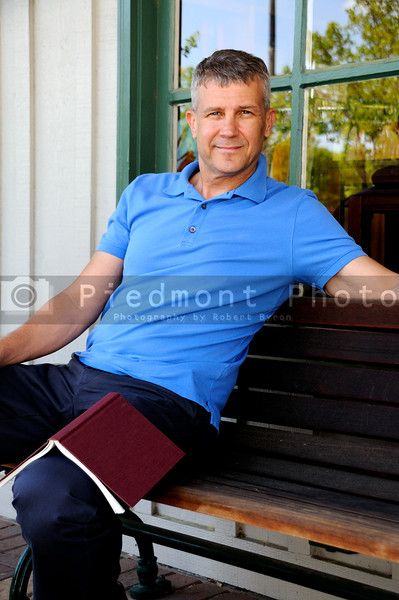 A handsome man sitting on a bench in front of a building