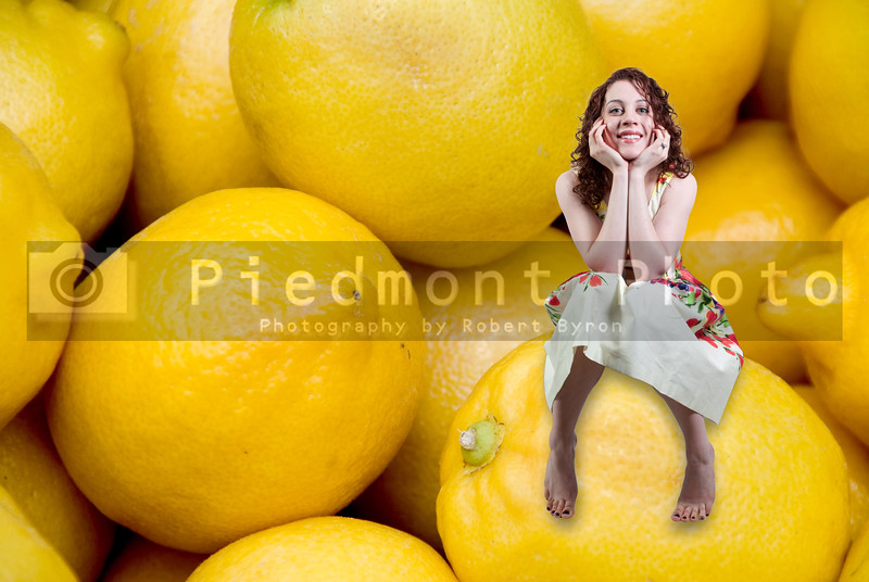 A woman sitting on a pile of delicious lemons