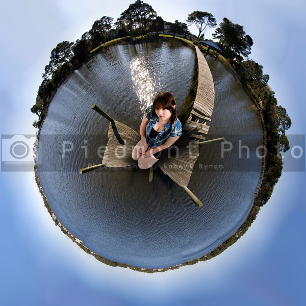 A beautiful young woman sitting in a circular panorama of a coastal area.