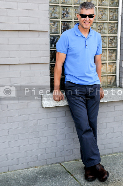 A handsome middle aged man leaning on a wall.