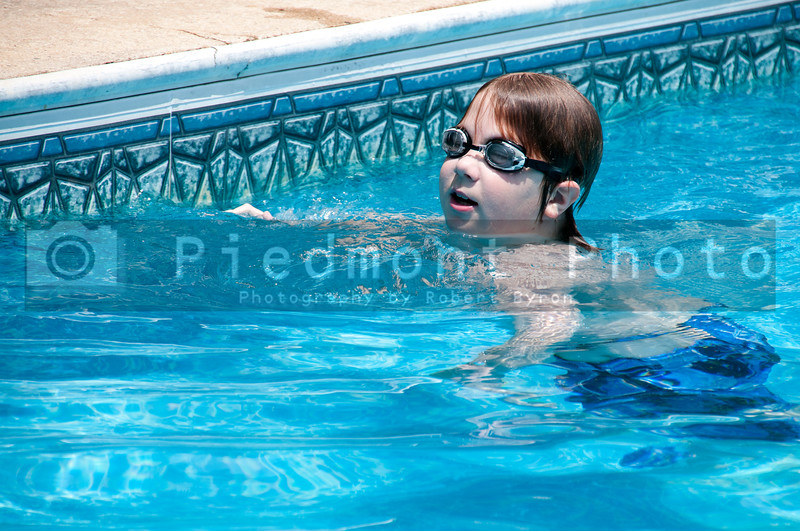 A little boy swimming in a pool.