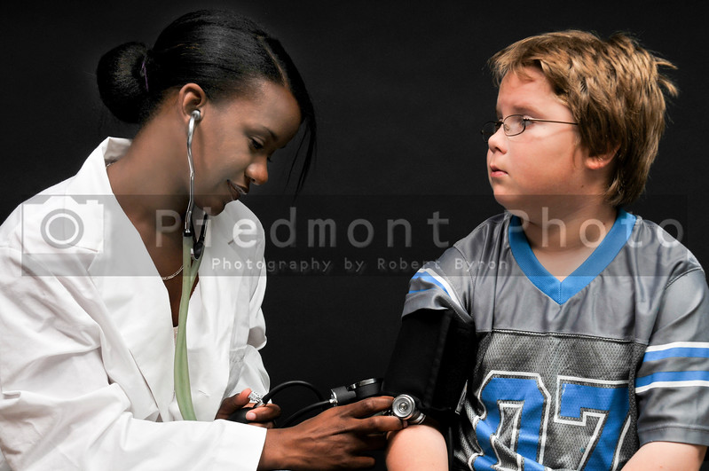 A beautiful young doctor taking a childs blood pressure