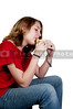 A beautiful teenage girl with braces eating a sanswich