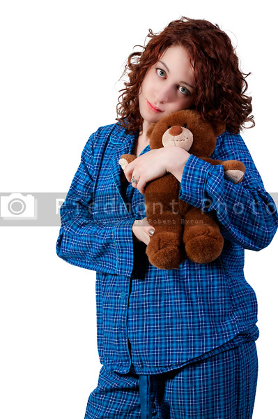 A beautiful young woman wearing pajamas hugging her stuffed teddy bear
