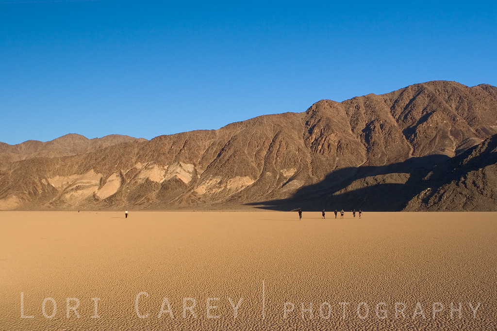 "A group of adventurers set off across the Racetrack Playa in Death Valley National Park, California in search of the mysterious moving rocks. Although the rocks slide slowly across the dried mud surface of the playa, leaving visible tracks behind, no one has ever actually seen them moving. <br><br> <a href='http://www.licensestream.com/LicenseStream/client/contentDisplay.aspx?cid=12462&fid=13175&l=r'><font color=""red"">License this Image</font></a>"
