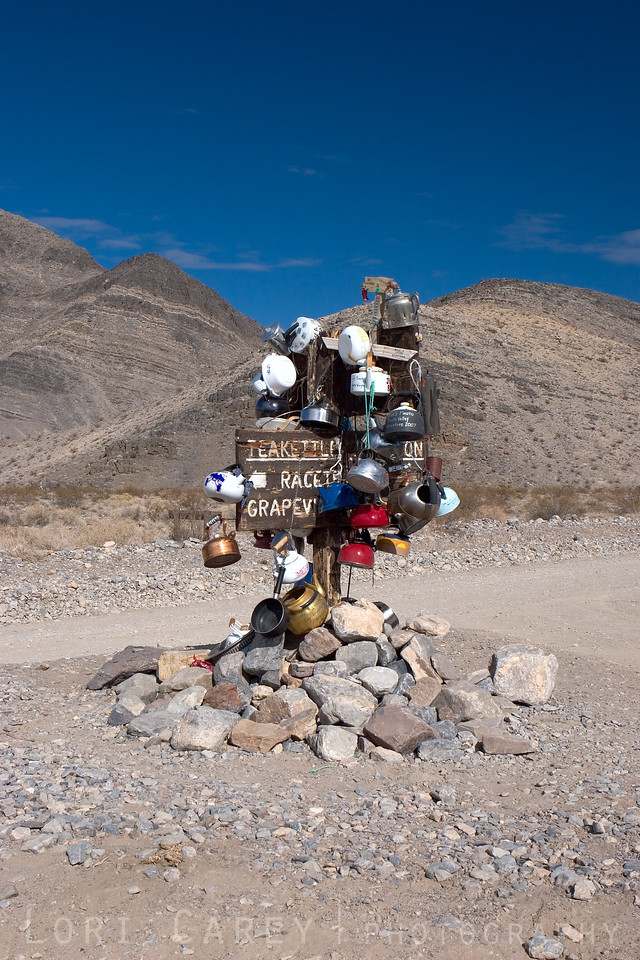 Teakettle Junction at the intersection of Racetrack Road and Hidden Valley Road in Death Valley National Park. Visitors place decorated teakettles on the sign post. From time to time the park rangers remove them, so the collection is always evolving.