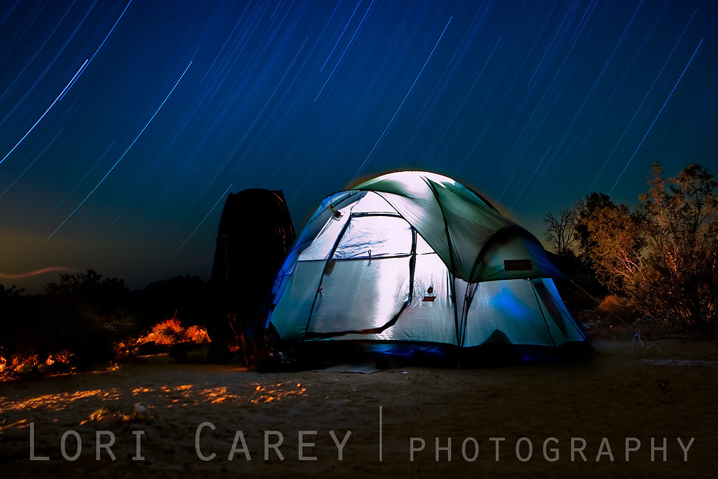 Night shot of tent with light painting and star trails at Kelso Dunes in the Mojave National Preserve.