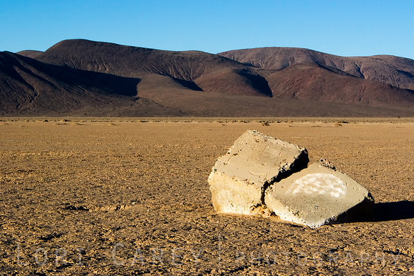 Cement blocks with grafitti on Cuddeback Dry Lake, Almond Mountains in the background. Mojave Desert, California, USA