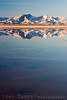 Snow-covered mountains reflected in East Superior Dry Lake in the Mojave Desert. This is usually a playa (a dry lake bed). A major winter storm brought snow to the Mojave Desert and turned the playa into a reflecting pool, creating this magical desert scene.