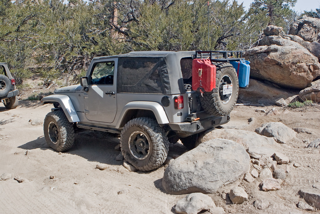 Jeep's rear bumper sitting on rocks; 33s aren't enough to clear this obstacle, 35s just make it