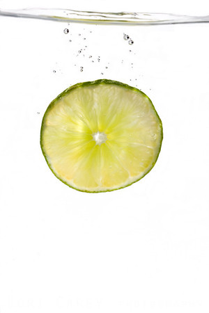 Mexican lime slice dropped into a tank of water, trailing bubbles, white background.