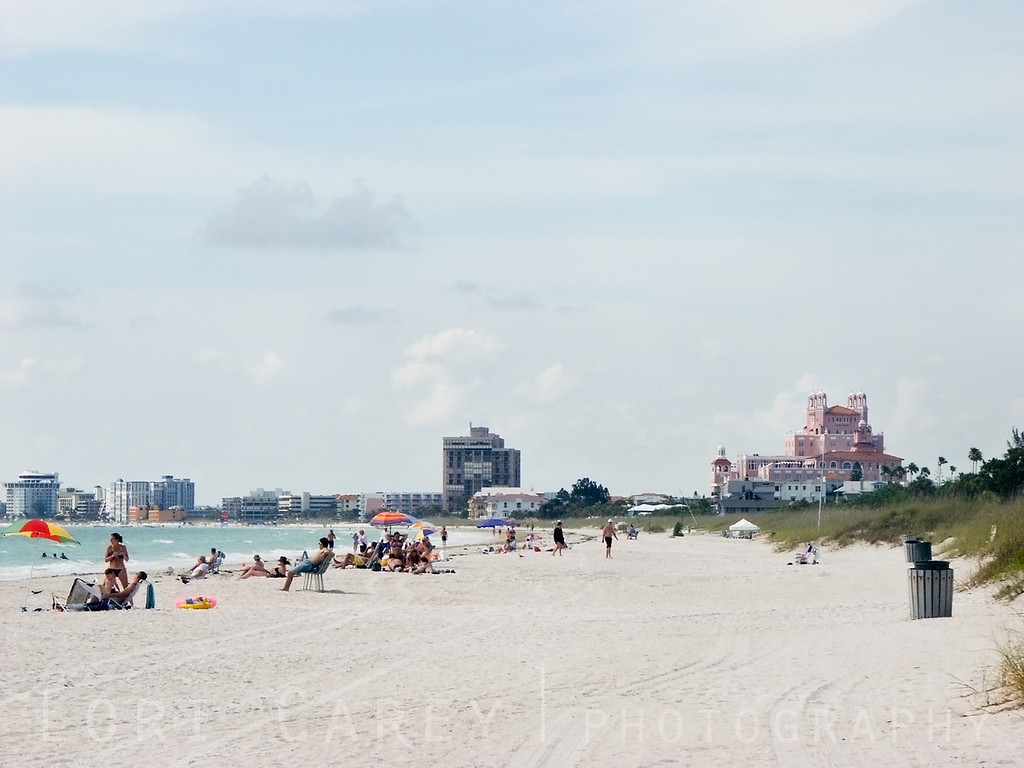 "Sunworshippers enjoy a summer afternoon on St. Pete's Beach, the legendary ""Pink Palace"", the Don Cesar Beach Resort in the background on the right. Saint Pete Beach, known as Long Key until 1957, is a barrier island off the mainland from St. Petersburg, Florida, situated between the Gulf of Mexico to the west and Tampa Bay to the east. It is a popular tourist destination for it's pristine white sand beaches and warm, clear Gulf water."