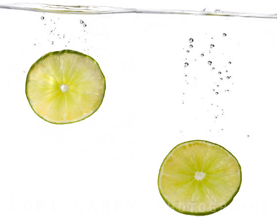 Composite image of two Mexican lime slices dropped into a tank of water with trailing bubbles and white background.