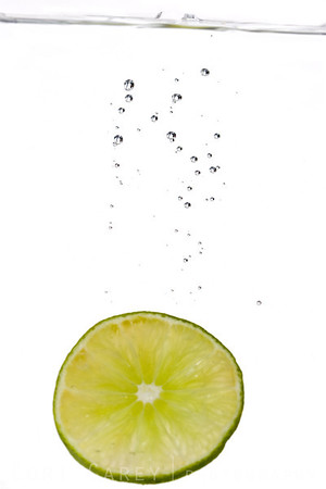 Mexican lime slice dropped into a tank of water, trailing bubbles, white background