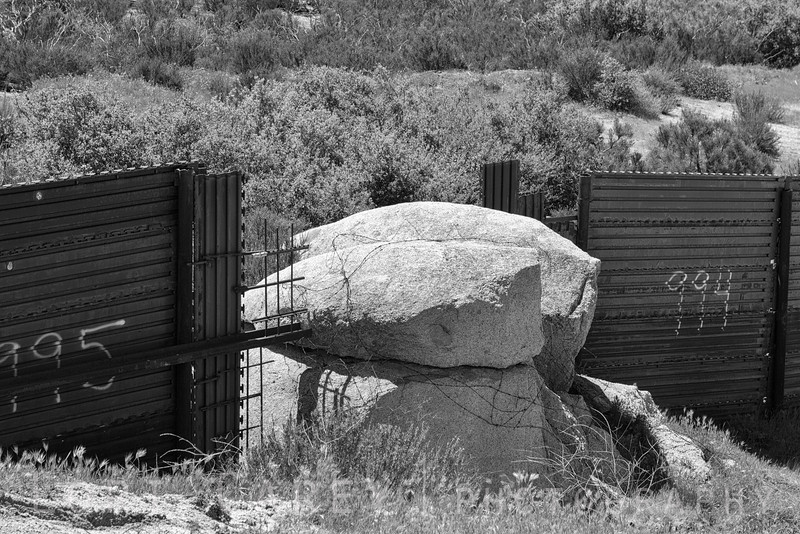Boulders and barbed wire in a section of the fence between the US-Mexico border in southern California