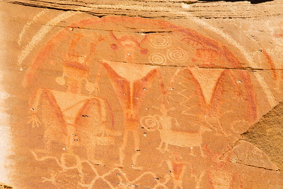 Anthropomorphic petroglyphs with painted features and rainbow, Molen Reef, Utah