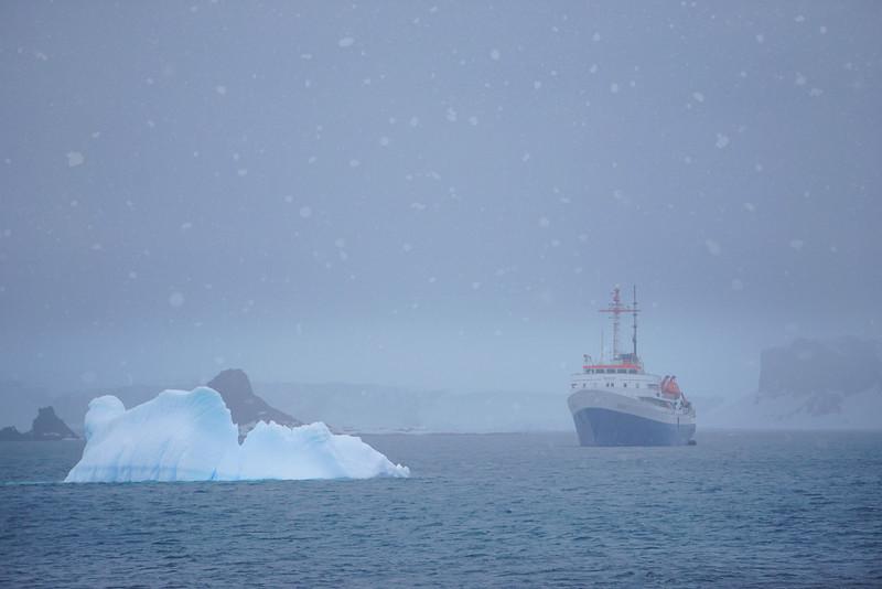 The Ushuaia Ship And Iceberg In Snow And Fog Barrientos Island in the South Shetlands, Antarctica Peninsula, Antarctica
