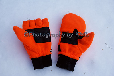 a apir of bright orange hunting gloves in the snow