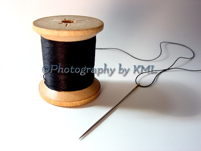 a threaded sewing needle with a spool of thread