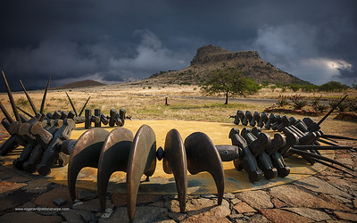 The Zulu monument at Isandlwana was designed by Pietermaritzburg sculptor Gert Swart, and consists of a circular concrete platform which symbolises the kraal of Zulu rural communities. Four bronze headrests and a bronze necklace echo the Zulu badge of honour, given by the King for acts of special valour. KwaZulu Natal. South Africa