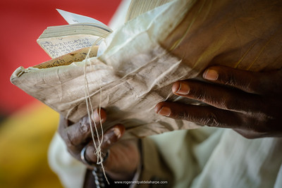 Man reading a bible at a Christian religious ceremony in a cave (where there is a source of Holy Water) at St. Neakutoleab Monestry near Lalibela. Ethiopia.