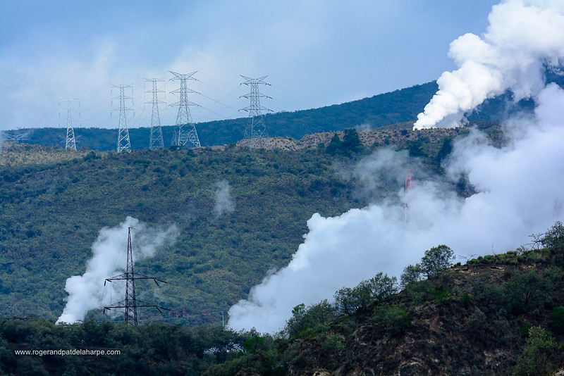 Plumes of geothermal steam and power lines from Olkaria geothermal power station . Hells Gate National Park. Naivasha. Great Rift Valley. Kenya
