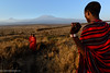 Maasai (Masai) elders with Mount (Mt) Kilimanjaro and Mount (MT)  Mawenzi (in Tanzania) on the left in the background. Satao Elerai Conservancy. Near Amboseli National Park. Kenya.