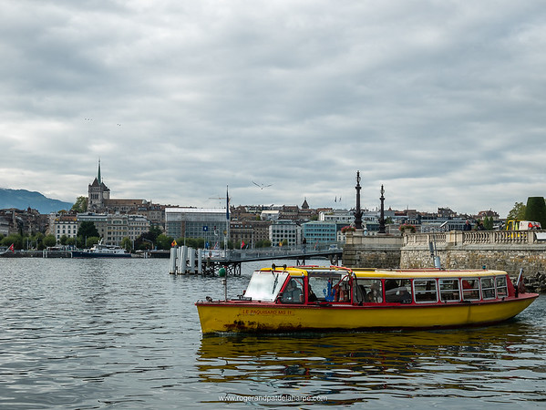 Public ferry on Lake Geneva with the Cathedral in the old city in the background. Geneva. Switzerland