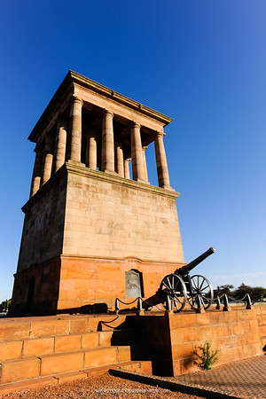 """Honoured Dead Memorial in honour of the soldiers who defended the city during the Anglo-Boer War. Built at the insistence of Cecil John Rhodes, the Honoured Dead Memorial is situated on the corner of Dalham and Oliver Roads. Designed by Sir Herbert Baker, it houses the vault that contains the remains of some British soldiers who died during the Siege of Kimberley. """"Long Cecil"""", the cannon at the base of the memorial, was built to defend the British against Boer artillery fire. The inscription on the memorial was written by Rudyard Kipling. Kimberley. Northern Cape. South Africa."""