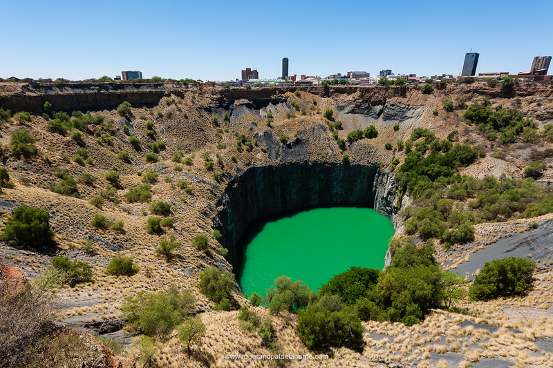 The Big Hole with the city in the background. Kimberley Mine Museum, was once a flat-topped hill and is now an awesome hole - the largest hand-dug excavation in the world - dug by picks, shovels and sheer determination, measuring 215 metres deep with a surface area of some 17 hectares and a perimeter of 1,6 km.  The Kimberley Mine site started on or about 16 July 1871 and by 14 August 1914 all mining activities ceased. By that time it had yielded 2 722 kilograms of diamonds extracted from 22,5 million tons of excavated earth. Kimberley. Northern Cape. South Africa.