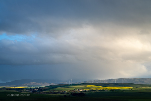 Image Number a7Riv403036. Storm clouds over farmlands and the Wind turbines on the 27 MW Klipheuwel Wind Farm. Near Caldon. Overberg. Western Cape. South Africa