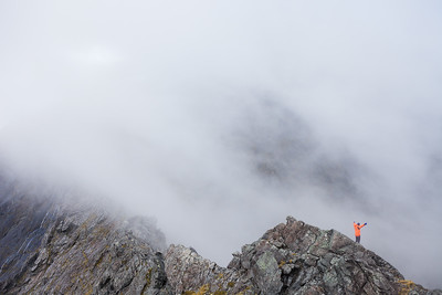 A climber stands alone on Homer Saddle with his arms in the air, Fiordland National Park
